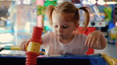 Portrait of a pretty little girl with ponytails playing with a gaming machine in the arcade. Concept of holiday for children and entertainment complexes. Full hd 1080 footage