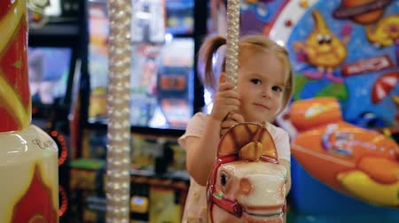 Happy little caucasian girl riding a horse carousel in the game room in the mall. The concept of celebrating a birthday of children and visiting entertainment complexes. Full hd 1080 footage