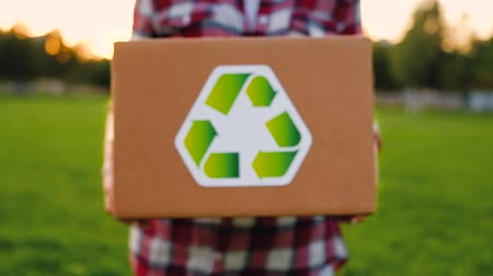caution sign : Unidentified woman pulls a cardboard box marked as recycled raw materials in a park on a warm summer day. The concept of environmentally friendly materials and nature conservation. Stock Footage