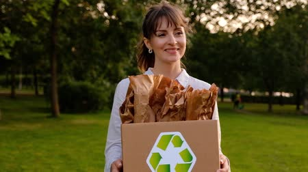 Happy beautiful young woman carries in her hands a box with paper bags with the icon of recyclable raw materials and walks in the park on a summer warm day. Environmental care concept.