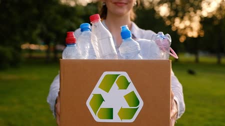 Young unidentified woman holds in hands a box with plastic bottles with the icon of recyclable materials in the park on a summer warm day. Environmental Protection Concept. Full hd 1080 footage Wideo