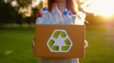 azaltmak : Young unidentified woman holds in hands a box with plastic bottles with the icon of recyclable materials in the park on a summer warm day. Environmental Protection Concept. Full hd 1080 footage Stok Video