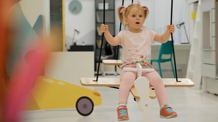 Charming little girl sways on a swing in the form of an airplane in a childrens playroom and rejoices. The concept of childrens entertainment and holidays. Full hd 1080 footage