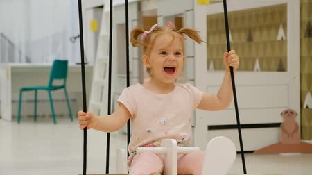 Laughing little girl swinging on a swing in the form of an airplane in a childrens playroom and laughing while looking at the attendants. The concept of childrens holidays and family time.