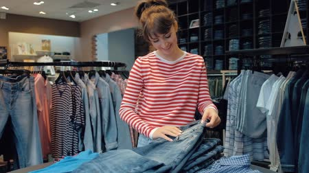 Happy young woman seller in denim boutique leafing through a stack of jeans while working in a denim clothing store. The concept of comfortable work for a young woman. Full hd 1080 footage Wideo