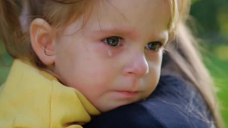 Cose-up portrait of a beautiful little two-year-old girl crying in her mothers arms while walking. Baby Care Concept. Full hd 1080 footage