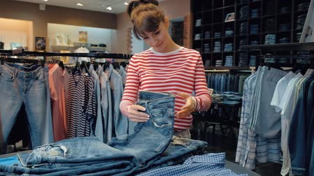 krásná žena : Young female seller in a denim store flips through a stack of denim pants during the sales season. Concept of work in a luxury clothing store. Full hd 1080 footage