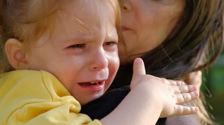 Close-up portrait of a cute crying little girl sitting in her mother arms while walking on a summer day in the park. The concept of child abuse violation of childrens rights. Full hd 1080 footage Wideo