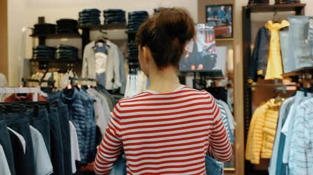 Rear view of a young beautiful fit woman sales assistant consultant in a clothing store hangs out clothes after trying on of visitors. Concept of work in a clothing store in a shopping center.
