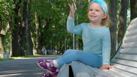 Cute smiling little girl in blue clothes joyfully shows her age on her fingers while sitting on a park bench on a warm summer day. The concept of cheerful carefree children. 4k footage