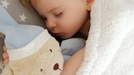Close-up of a cute sleeping beautiful girl on a pillow with a bear in the middle of the night. The concept of caring for children. Healthy or sick baby. 4k footage