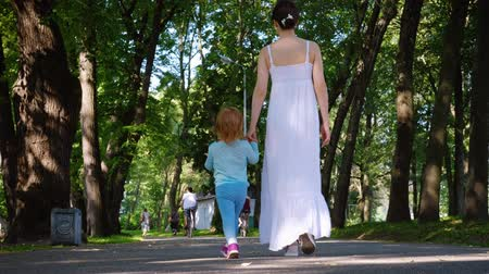 Rear view of a young mother in a long white sundress walks by the hand with her charming daughter in a blue suit. Family vacation in the park concept. 4k footage