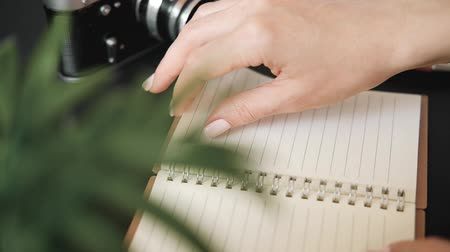 Close-up of the hand of a young unknown woman sitting at a table surrounded by plants and a film camera turns over a page of a notebook. The concept of maintaining a personal diary and memo notes. Wideo