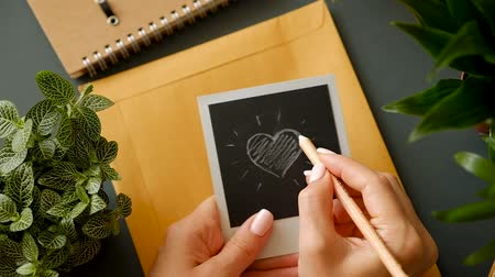 Closeup of the hand of a young girl with a beautiful manicure draw a heart on a photograph above a table with a mail envelope and office supplies. Love message concept. Full hd 1080 footage