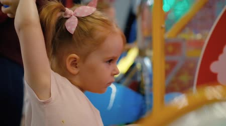 Little cute girl plays a slot machine during a holiday in the games room with her parents. The concept of addiction to gadgets and modern high-tech toys. Full hd 1080 footage Wideo