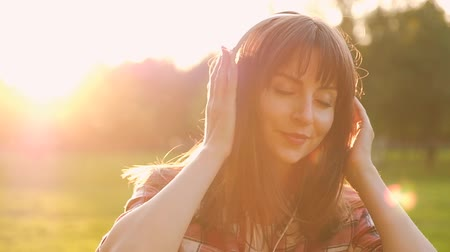 Portrait of a beautiful sensual young woman listening to music through headphones while walking in the park on a sunny warm summer day. Music Subscription Concept. Full hd 1080 footage