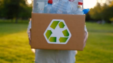 çöplük : Young unidentified woman holds in hands a box with plastic bottles with the icon of recyclable materials in the park on a summer warm day. Environmental Protection Concept. Full hd 1080 footage Stok Video