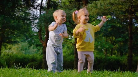 Cheerful beautiful little children brother and sister are dancing and having fun
