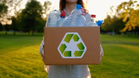 Young unidentified woman holds and hands a box with plastic bottles Dostupné videozáznamy