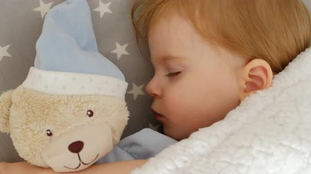 peluş : Close-up of a cute sleeping beautiful girl on a pillow with a bear Stok Video