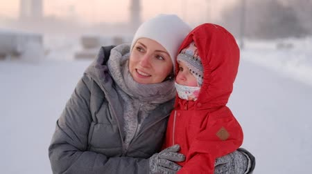 bir kişi : Caring young mother in winter clothes walks with her charming daughter Stok Video