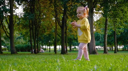 Charming pretty little girl dancing and rejoicing while walking in the park