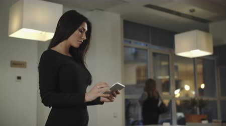 стоять : Business woman standing in the office and talking with a tablet. UHD