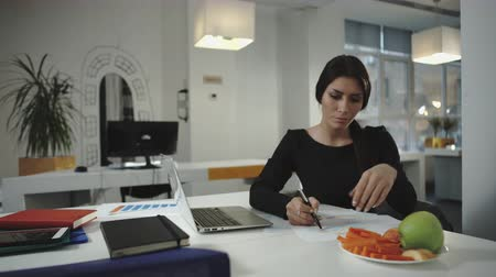 havuç : Woman working and eating slices of carrots and apples. UHD Stok Video