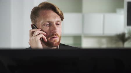 makler : Red-haired man sitting at a computer and calling on the phone. UHD