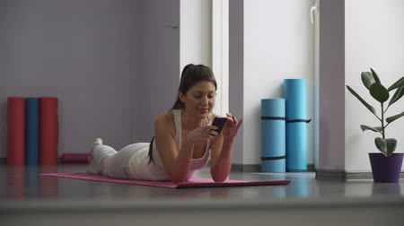 применения : Girl lying on the yoga mat and looking at the phone.