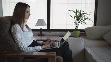 munkaruha : Woman with long hair at home sitting and working  near panoramic windows . Her hands with short pink nails lying on the armchair. She is typing on the laptop. Female dressed  in white shirt and black trousers formal business clothes.