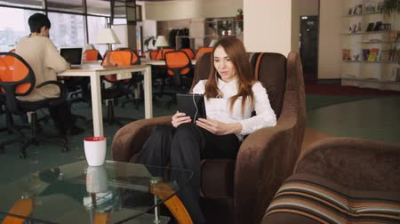 ül : Business woman at the office speaking with partner on the tablet computer using earphone. Female sit on the sofa and drink coffee. She is smiling  and looks happy. On the background her assistant  with short black hair sitting at working place  working wi