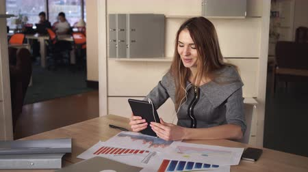 консультант : Business woman using app on the touch screen tablet. On her desk documets and charts with sales report