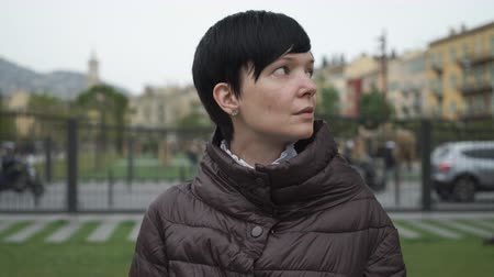 hiç kimse : Caucasian model with short black hair dressed jacket day time. Spring season. Female in the park on green grass walking pigeons. On the background buiding and road with cars. Stok Video