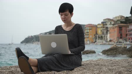 autor : Frenchwoman using laptop at her vocation in Nice Cote dAzur Provence. Female sitting on the beach read news check mail. On the backgroung view city.