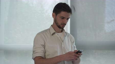 cellphone : Handsome young male using app on smartphone for send message. He stands near the windows in the office.