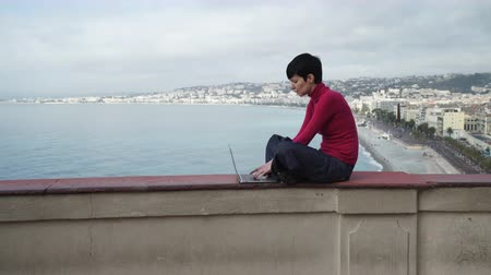 autor : On the background city view with blue sea and sky with clouds. Female freelancer working in the open air.