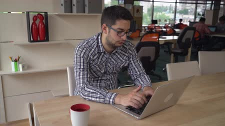 рабочих мест : Handsome man mixed race typing on the computer at his working place. On the background colleagues work with laptop. Brunet with eyeglasses on his face. Behind young male wooden sh