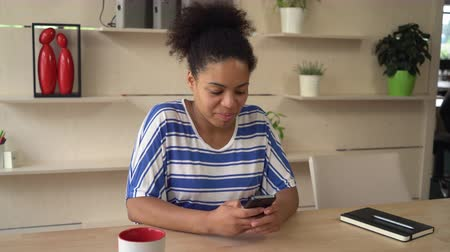 pessoas reais : Female smiling and writing message on the smartphone. Mixed race businesswoman texting sms and read email at the working place with wooden table. Girl wearing in casual dress with blue strips.