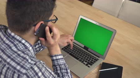 fából készült asztal : Young professional worker in the office has call negotiation with client looking on the laptop green screen. Manager has conversation with customer on the smartphone sitting near the wooden desk with modern device.Worker wear in casual plaid shirt with gl Stock mozgókép