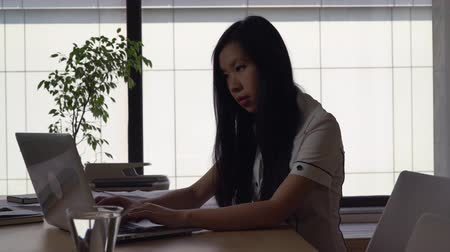 sucessful : Attractive professional business woman typing on the computer. Successful manager in international holding or startup company reading documents. Female sitting at the big desk with glass of water. Mixed race model wearing in formal casual clothes white sh