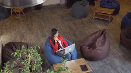 паркет : Asian female working on computer. Upper top view. Young professional girl typing on laptop in warehouse office with wooden furniture and parquet,color bean bag chairs.