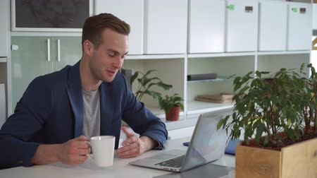 chatting : Successful businessman using app on computer for remote meeting. Handsome caucasian male talking emotionally with client and smiling. Professional worker or head department consult with financial advisor online. Stock Footage