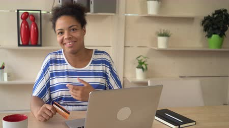 bancos : Joyful african mixed race female shopping online in office or home with wooden modern design. Laughing young girl buy via internet in apartment. Attractive multicultural model wearing in casual top with blue and white stripes. Mulatto satisfied customer l