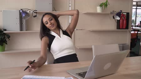 multikulturális : Mixed race woman in the office sitting a the working space. On her desk computer and charts, diagrams on the paper report. Young professional female at the work. Attractive worker wearing in elegant fashionable dress.