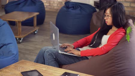 kodlama : Young asian girl chatting in social net on computer use wifi. Student or worker work with office equipment. Happy vietnamese model wearing in casual jeans and red top. She concentrated on her project. Her finders computing fast and she created new softwar