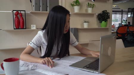 ügynökség : Female looking on blueprint and checking with electronic version on computer. Asian young professional designer works at the working place with table laptop . Multicultural smiling worker wearing in casual white shirt and black trousers