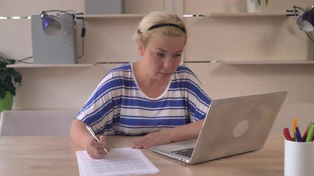 haywire : Business woman at the office working with paper documents she upset and frustration about her work. Female writing notes on the report than irritated and annoyed crumples paper looking with haywire on the screen computer. Caucasian businesswoman middle ag