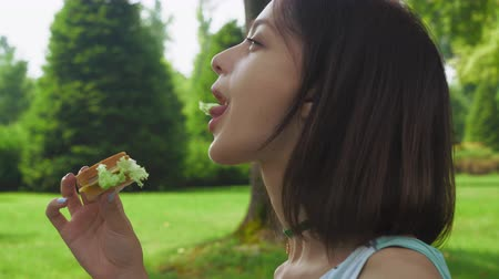 nyel : Young brunette girl sitting sideways in the park on a sunny day and eat a sandwich with salad. Close up.