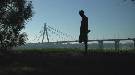 shaves : Silhouette of a young athletic guy that trains and stretches his legs outdoors next to the tree. In the background is seen as the bridge leaving the car. Man doing workout berofe start run.